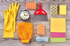 Spring cleaning background with supplies. Close up colorful house cleaning products and alarm clock. Time for a spring clean Stock Photos