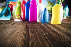 Spring cleaning. Spring cleanup theme. Variety of colorful house cleaning products on a rustic wooden table and blue background Stock Photos