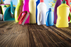 Spring cleaning. Spring cleanup theme. Variety of colorful house cleaning products on a rustic wooden table and blue background Royalty Free Stock Photography