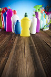 Spring cleaning. Spring cleanup theme. Variety of colorful house cleaning products on a rustic wooden table and blue background Stock Photo