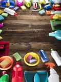 Spring cleaning. Spring cleanup theme. Variety of colorful house cleaning products on a rustic wooden table. Top view Stock Photo