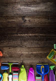 Spring cleaning. Spring cleanup theme. Variety of colorful house cleaning products on a rustic wooden table. Top view Stock Photos