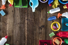 Spring cleaning. Spring cleanup theme. Variety of colorful house cleaning products on a rustic wooden table. Top view Stock Photography