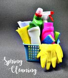 Spring cleaning concept.Colorful set of cleaning supplies in a blue basket with text. Selective focus Stock Image