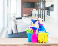 Spring cleaning concept. Colorful spays and rubbers on wooden table in open space apartment Stock Photography