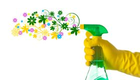 Spring cleaning concept. Floral detergent sprayed by a hand with. Yellow glove Stock Photos