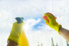 Spring cleaning concept. Spring cleaning - someones hands in yellow gloves cleaning window Stock Photography