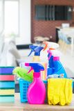 Spring cleaning concept. Colorful spays and rubbers on wooden table in apartment Stock Photo