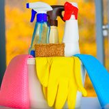 Spring cleaning concept with supplies over floral background. stock photos