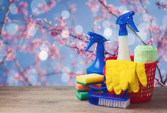 Spring cleaning concept with supplies over floral background Royalty Free Stock Photo