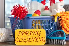 Spring cleaning concept with supplies. House cleaning items in basket and paper card with text spring cleaning. Cleaning service concept Royalty Free Stock Photo