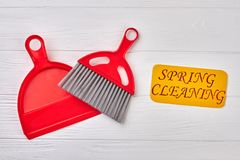 Spring cleaning concept with supplies. Red plastic scoop and brush on white wooden background. Cleaning service concept Stock Photography