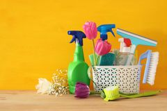 Spring cleaning concept with supplies on wooden table. Royalty Free Stock Photo