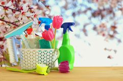 Spring cleaning concept with supplies on wooden table. Royalty Free Stock Photography