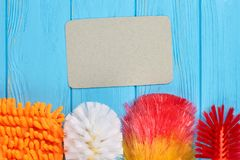 Spring cleaning equipment on colorful background. Set of multicolored brushes for house cleaning and empty paper card. Housekeeping and cleaning concept Stock Photography