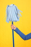 Spring cleaning mop. Cleaning concept. Woman holding cleaning mop on yellow background Royalty Free Stock Images