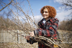 Spring cleaning the orchard. Farmer woman cleaning the branches in an orchard after pruning Royalty Free Stock Photography