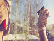 Spring cleaning - cleaning windows. Women`s hands wash the window, cleaning. Spring cleaning - cleaning windows. Women`s hands wash the window Stock Photo