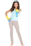 Spring cleaning woman fun. Spring cleaning woman pointing cleaning spray bottle shooting at camera. Beautiful cleaning girl standing in full body isolated on Stock Photography