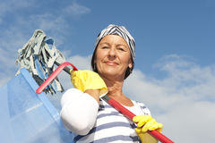 Spring cleaning woman outdoor. Portrait mature cleaning lady outdoor at spring time, with bucket, mop and bandana,  with blue sky as background and copy space Stock Photography