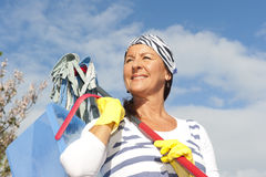 Spring cleaning woman outdoor. Portrait mature cleaning lady outdoor at spring time, with bucket, mop and bandana,  with blue sky as background and copy space Stock Photo