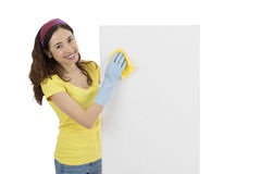 Spring cleaning woman wiping a blank advertising board. Friendly cleaning woman washing a blank white billboard Royalty Free Stock Photography