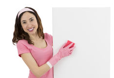 Spring cleaning woman wiping the blank advertising board. Smiling happy caucasian cleaning woman washing the white blank advertisement poster Royalty Free Stock Photography