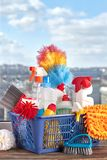 Spring cleanup theme. Variety of colorful house cleaning products on window background royalty free stock photo
