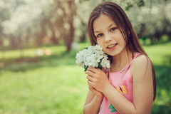 Spring closeup outdoor portrait of adorable 11 years old preteen kid girl. Spending spring holidays in beautiful blooming cherry garden Royalty Free Stock Images