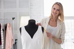 Merry female dressmaker designing dress. Spring collection. Joyful female dressmaker posing near mannequin while using meter Royalty Free Stock Photo