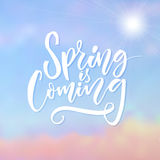 Spring is coming. Inspirational caption at blue sky background with sun. Brush lettering design. Stock Photo