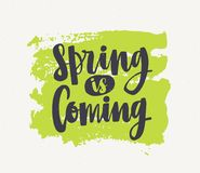 Spring Is Coming lettering written with elegant cursive font or script on green paint smear isolated on white background. Handwritten springtime inspirational Stock Photos