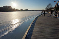 Spring is Coming Soon. Photo of afternoon sun, melting ice and people at the georgetown waterfront in washington dc on in late february. The winter of 2015 has stock photos