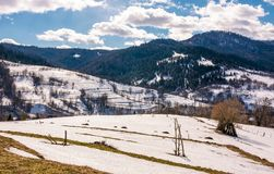 Last days of winter in rural landscape. Spring is comming. last days of winter landscape. rural field with weathered yellow grass covered with snow. village at Royalty Free Stock Photos