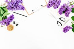 Spring composition with clipboard, scissors, lilac flowers and accessories on white background. Spring time. Flat lay, top view. Spring composition with stock photography