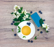 Spring composition of cup of tea, notebook and flowers on wooden table, flat lay Stock Images