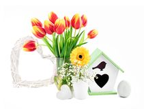 Spring composition with flowers, nesting box, egg and heart, iso Stock Image