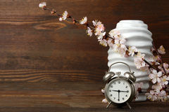 Spring composition. Old windup loud alarm clock with a sprig of peach and vase on wooden background Royalty Free Stock Images