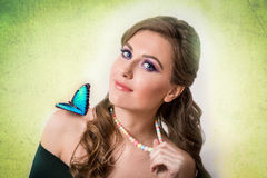 Spring concept of a blonde woman with a blue butterfly and a col. Spring concept of a sensual blonde woman with a blue butterfly colorful necklace on green Royalty Free Stock Image