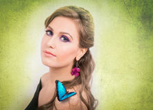 Spring concept of a blonde woman with a blue butterfly and a flo. Spring concept of a sensual blonde woman with a blue butterfly and a flower earing on green Stock Image