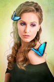 Spring concept of a blonde woman with a blue butterfly on her ha. Spring concept of a sensual blonde woman with a blue butterfly her hair and shoulder on green Royalty Free Stock Images