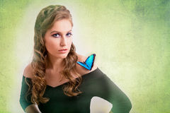Spring concept of a blonde woman with a blue butterfly on her sh. Spring concept of a sensual blonde woman with a blue butterfly on her shoulder on green Stock Photography