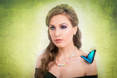 Spring concept of a blonde woman with a blue butterfly. Spring concept of a sensual blonde woman with a blue butterfly on green background Royalty Free Stock Images