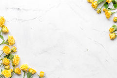 Spring concept with flowers on white marble table background top view mockup. Spring concept with yellow flowers on white marble table background top view mockup royalty free stock image