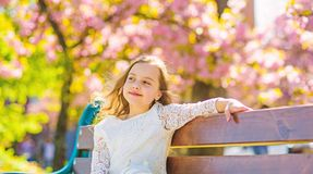 Spring concept. Girl on smiling face sits on bench, sakura tree on background, defocused. Girl relaxing while walk in. Park near cherry blossom. Cute child stock photo