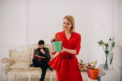Spring concept. Sensual woman hold spring flower while man reading book on sofa. Take care of flowers on spring season. Spring concept. Sensual women hold spring royalty free stock photography