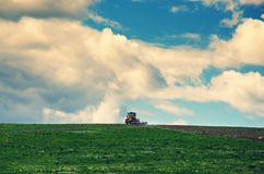Spring contry landscape with agriculture tractor cultivating field. stock photography