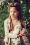 Spring country portrait of adorable dreamy kid girl near wooden fence with teddy bear Royalty Free Stock Photos