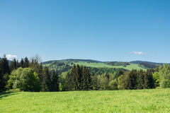 Spring countryside with pastures, trees and blue sky Royalty Free Stock Photos