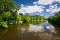 Spring countryside - river and blue sky with clouds Stock Image